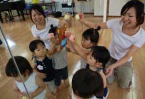 幼児リトミック教室風景。鏡に貼られた動物の絵に向かって参加者の女の子3人と先生。