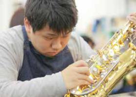 管楽器を修理する管楽器リペア科の学院生。