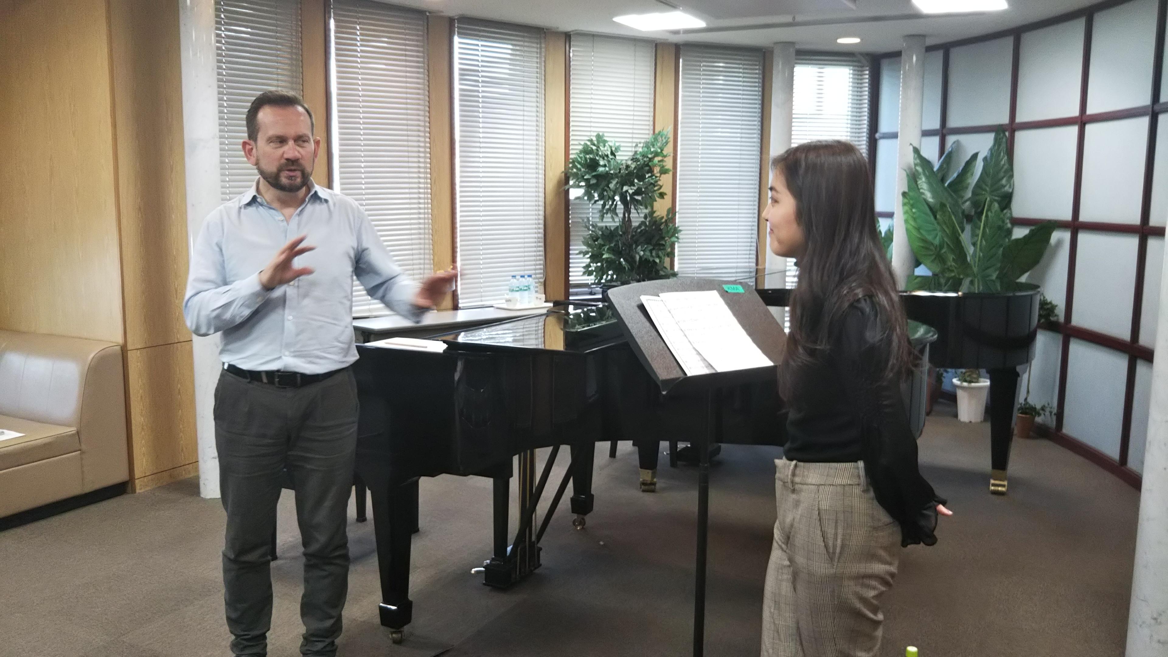 グランドピアノの前で身振り手振りを交えつつ、国立音楽院の在校生へ指導するジュリオザッパ氏。
