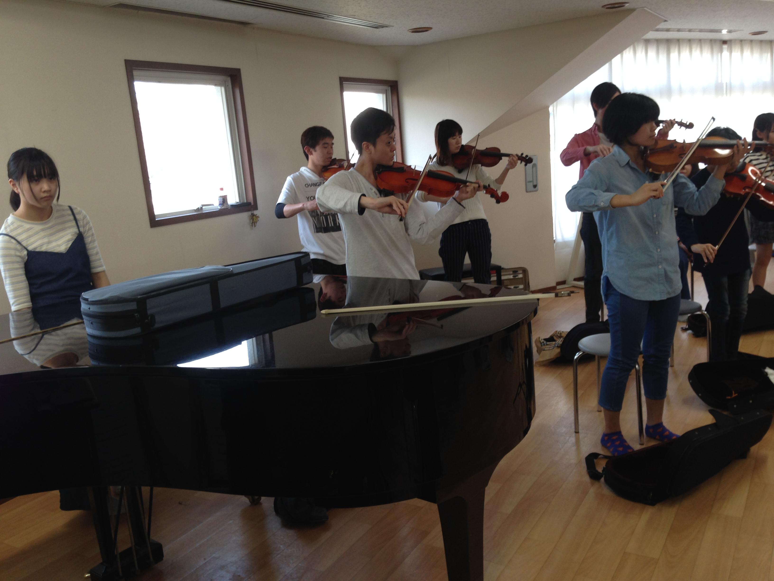 立って弦楽器を演奏する履修生達。