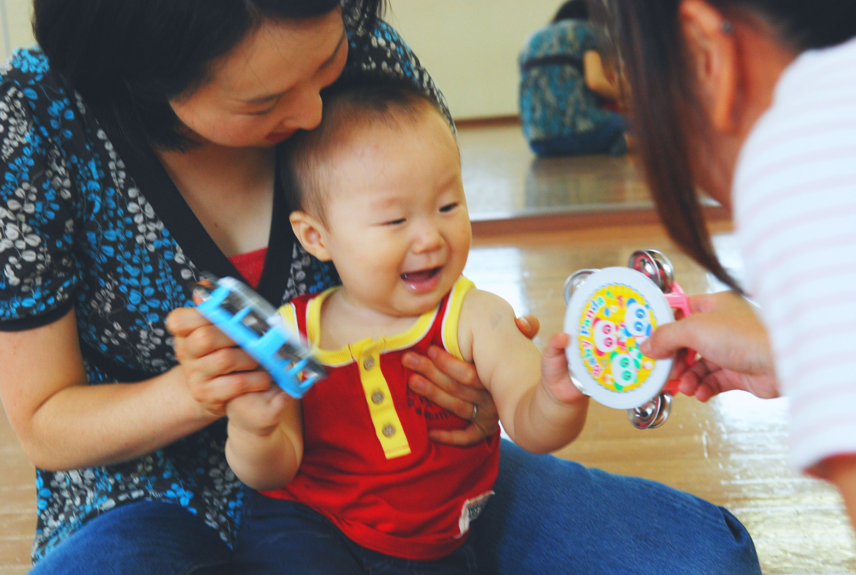 先生からタンバリンを手渡されている幼児。満面の笑顔で受け取っています。