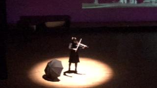 さくらホールの舞台上でスポットライトを浴び、エレキヴァイオリンを独奏する学生の姿。