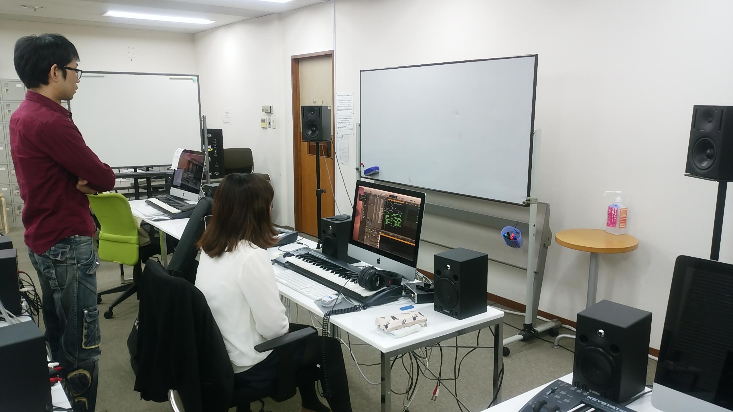 国立音楽院のDTM教室・コンピュータミュージック内で作曲ソフトLogicで自作曲を再生する学生と、それをチェックするDTM講師の福島先生。