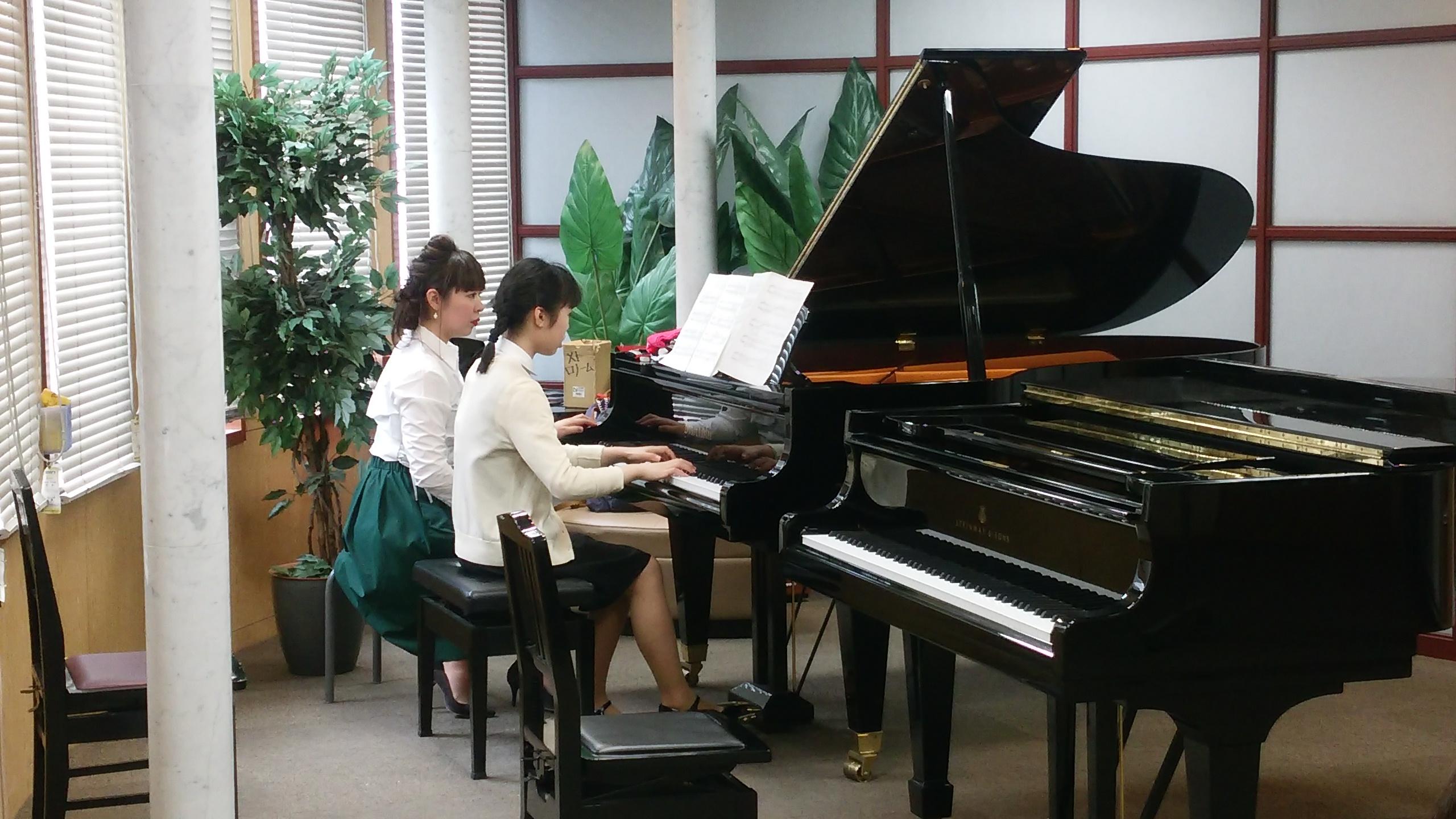グランドピアノが並ぶ国立音楽院ウイングルームで澤田講師が相原さんにピアノ指導している様子。