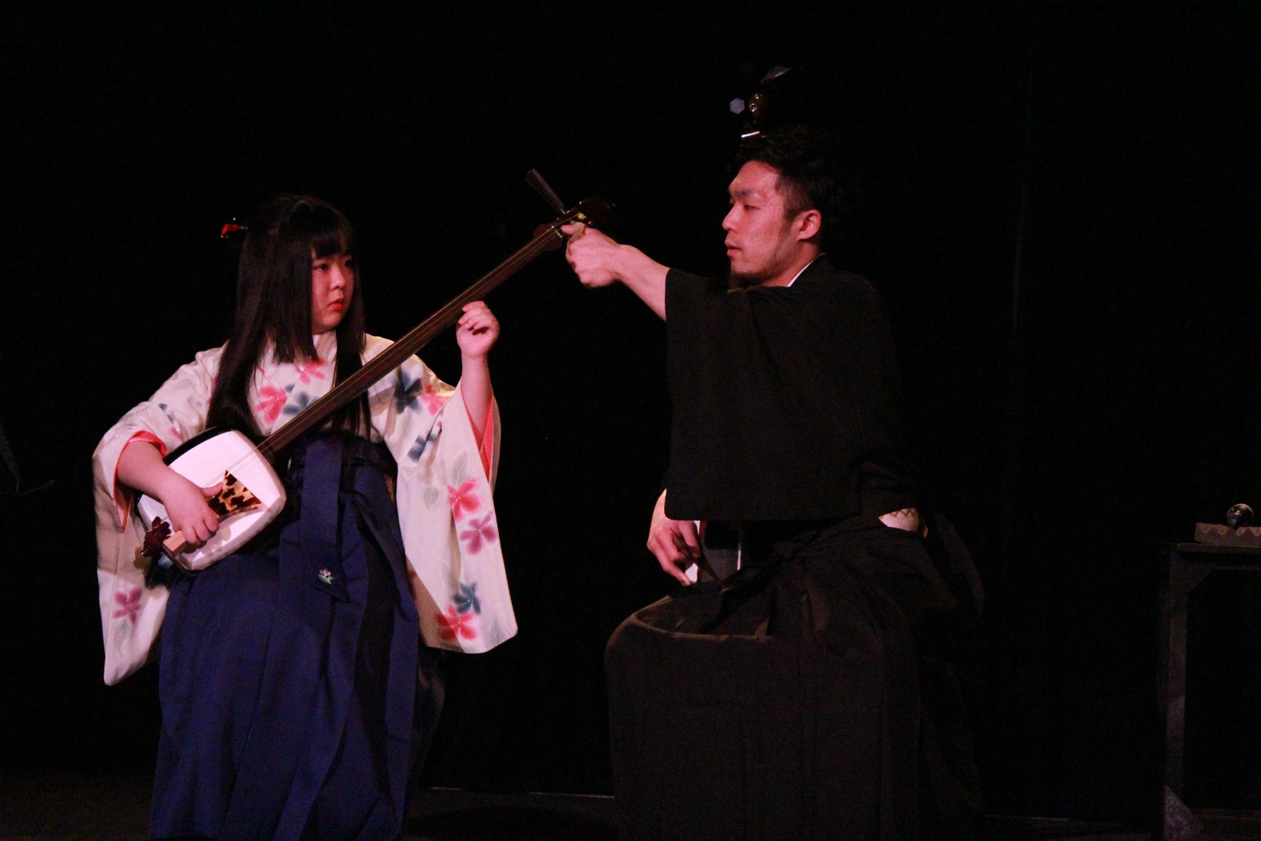 国立音楽院パラダイスホールのステージ上で三味線を構える高等部の学生と調弦をする桂城杜生先生。