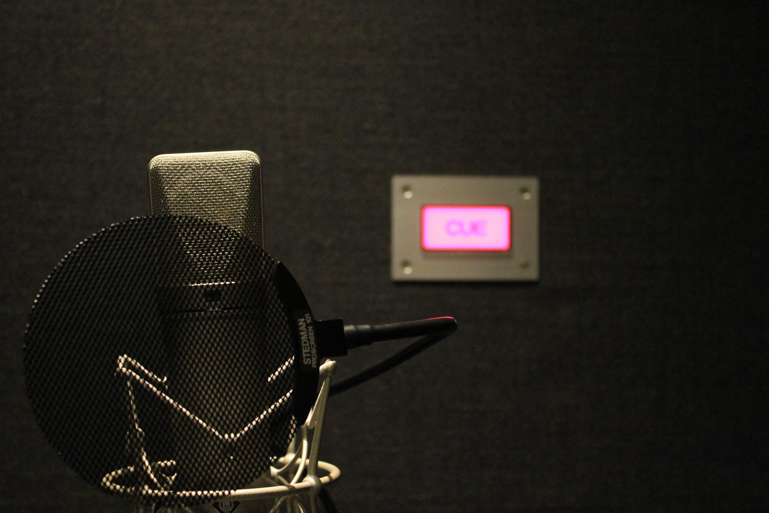 国立音楽院レコーディングスタジオ内のナレーション録音ブース。コンデンサマイクのNEUMANN U-87の奥にはCUEランプが光っています。