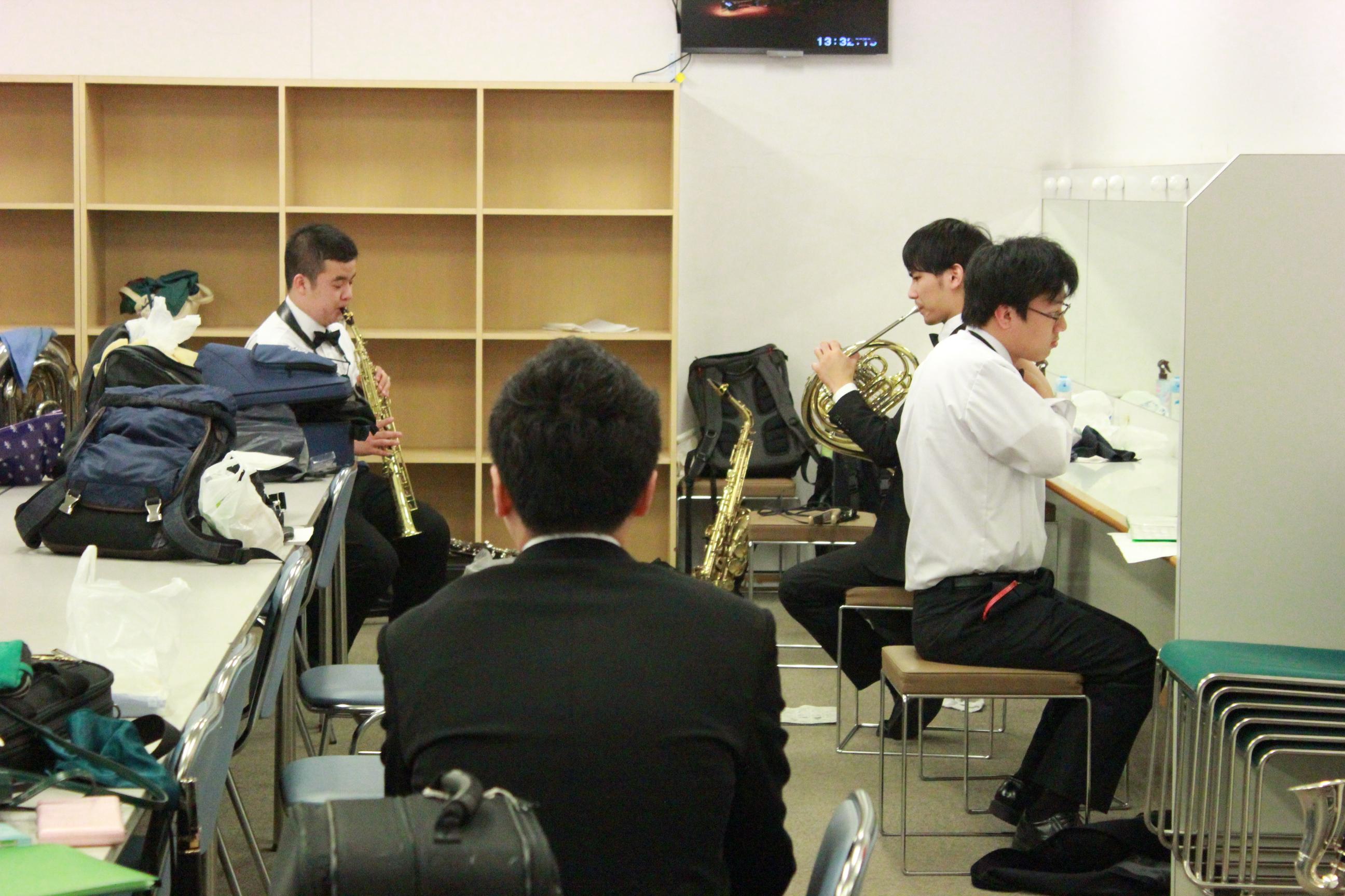 オペラシティコンサートホールの楽屋風景その2。学院生4名が鏡の前で身なりを整える姿や演奏の確認をする様子が写っています。