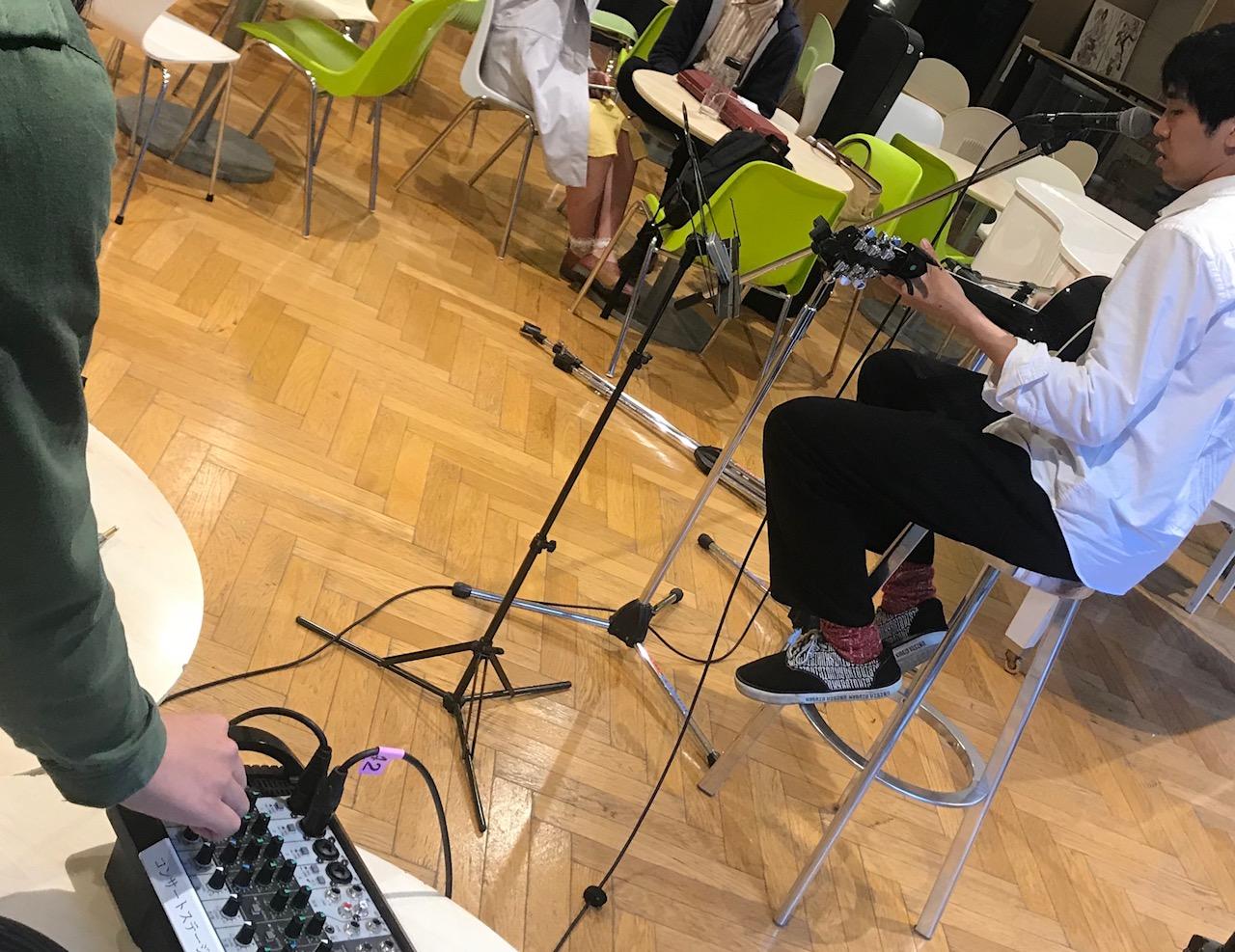 手前では体験に参加した方がミキサーを操作する様子、奥にはギターの弾き語りで音を出してみている源貴さんの様子が写っています。