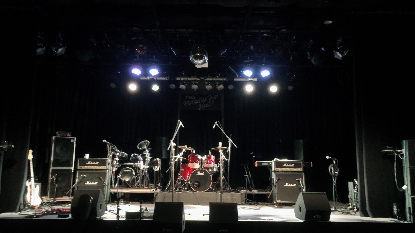 国立音楽院パラダイスホールのステージ。ツインドラム、ギターアンプ2発、キャビネットが2段積みのベースアンプ、キーボードなどがセッティングされています。