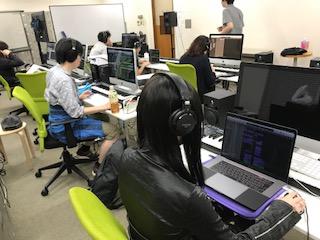コンピュータミュージック授業風景。ヘッドフォンを耳に、それぞれ制作作業に集中しています。