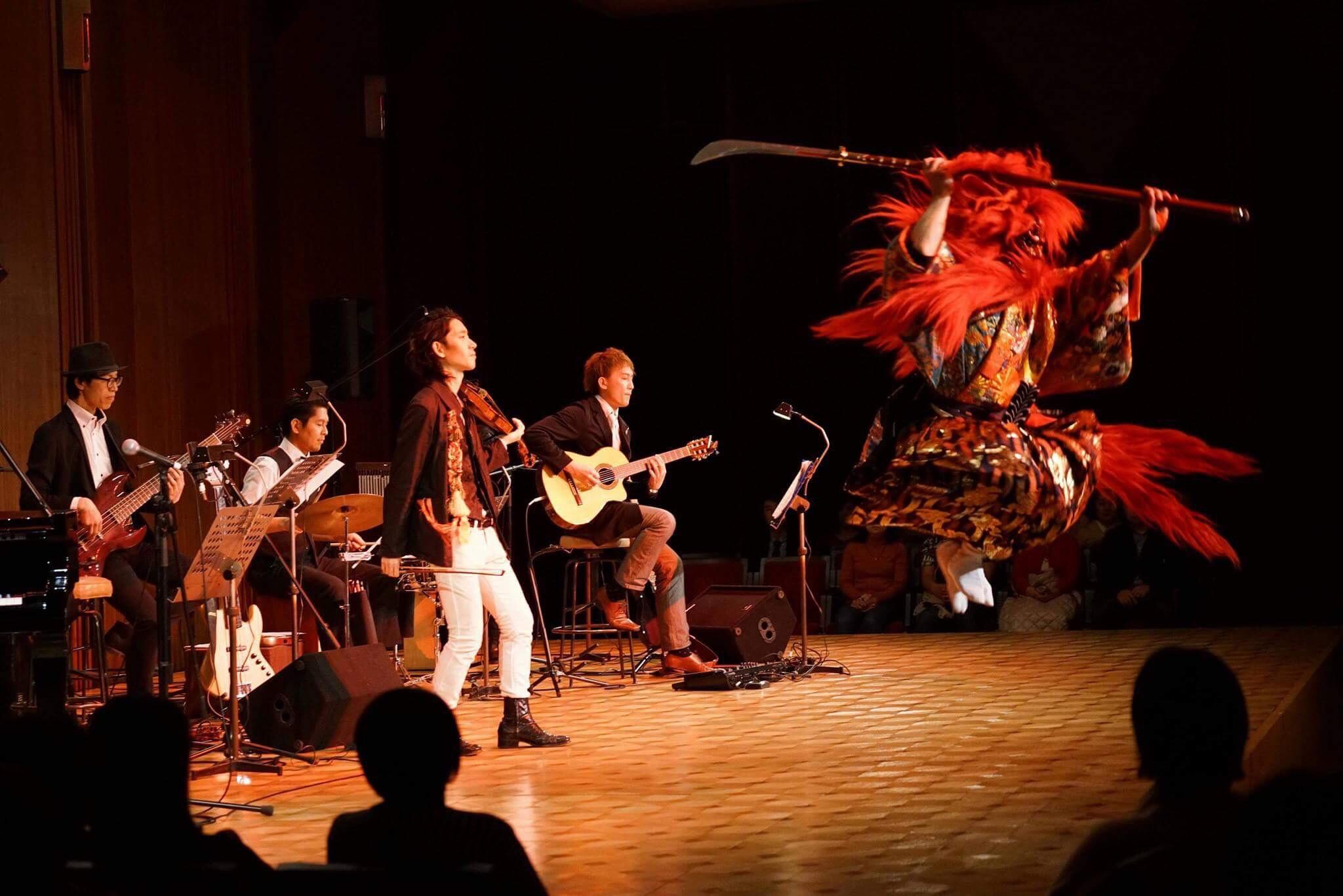 ヴァイオリン・ギター・ベース・ドラムなどによるバンド演奏の前でなぎなたを持った鬼神として舞う源講師。