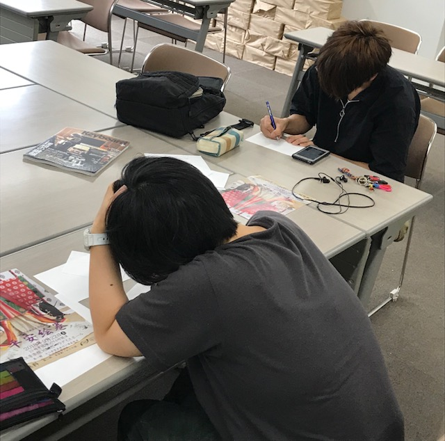 チラシのデザインを考える学院生2人の様子。頭を抱えつつ、紙の上にペンを走らせてみています。