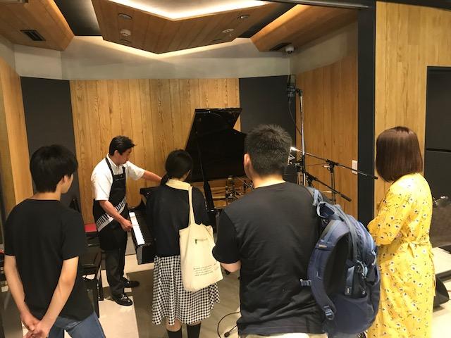 国立音楽院レコーディングスタジオ内に常設されたグランドピアノを使いピアノ調律師のお仕事を紹介する竹内淳講師と話を聞いている参加者の姿。ピアノにはマイクが沢山立てられています。