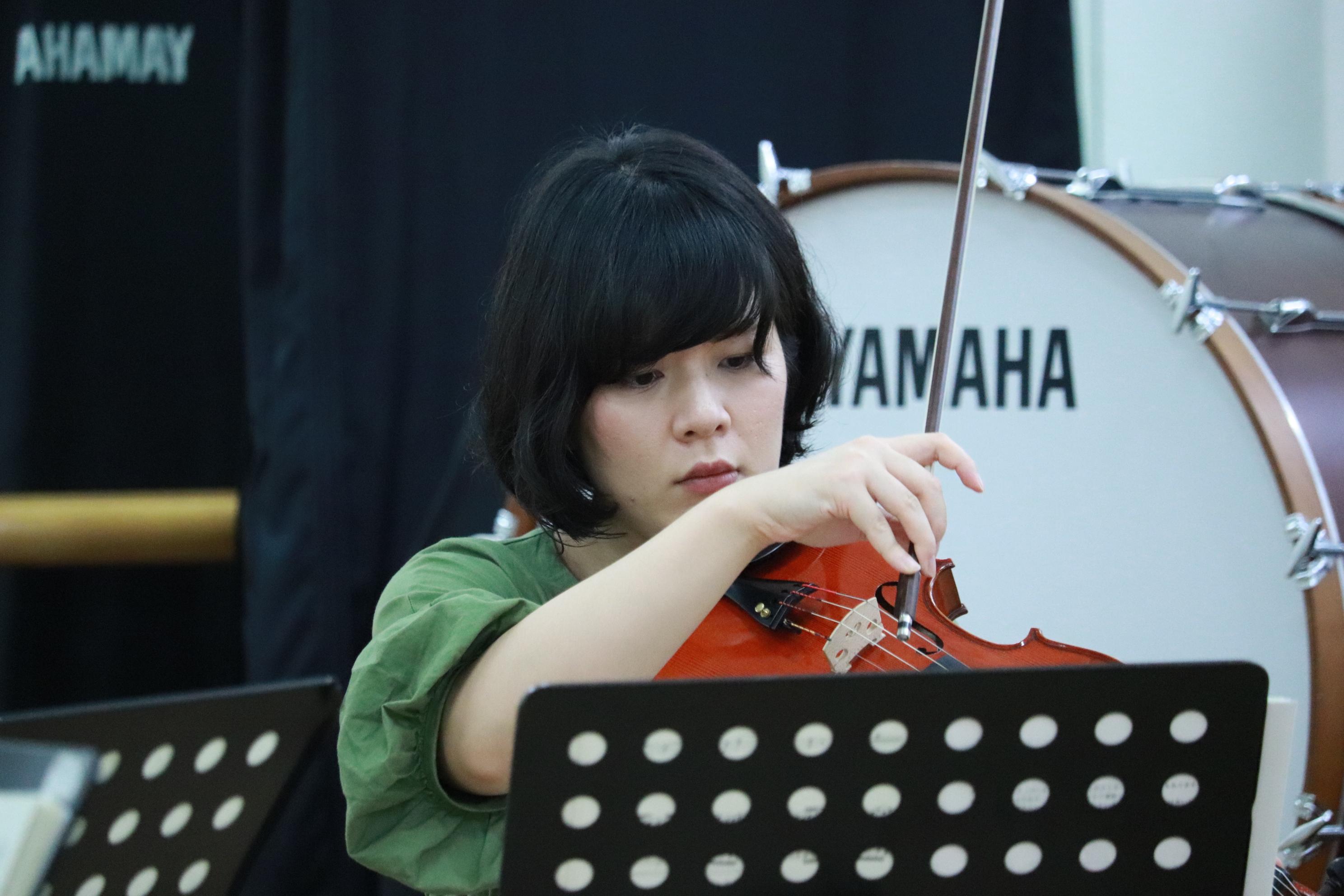 ヴィオラ奏者の女性を前方から撮影。ピチカートの瞬間。