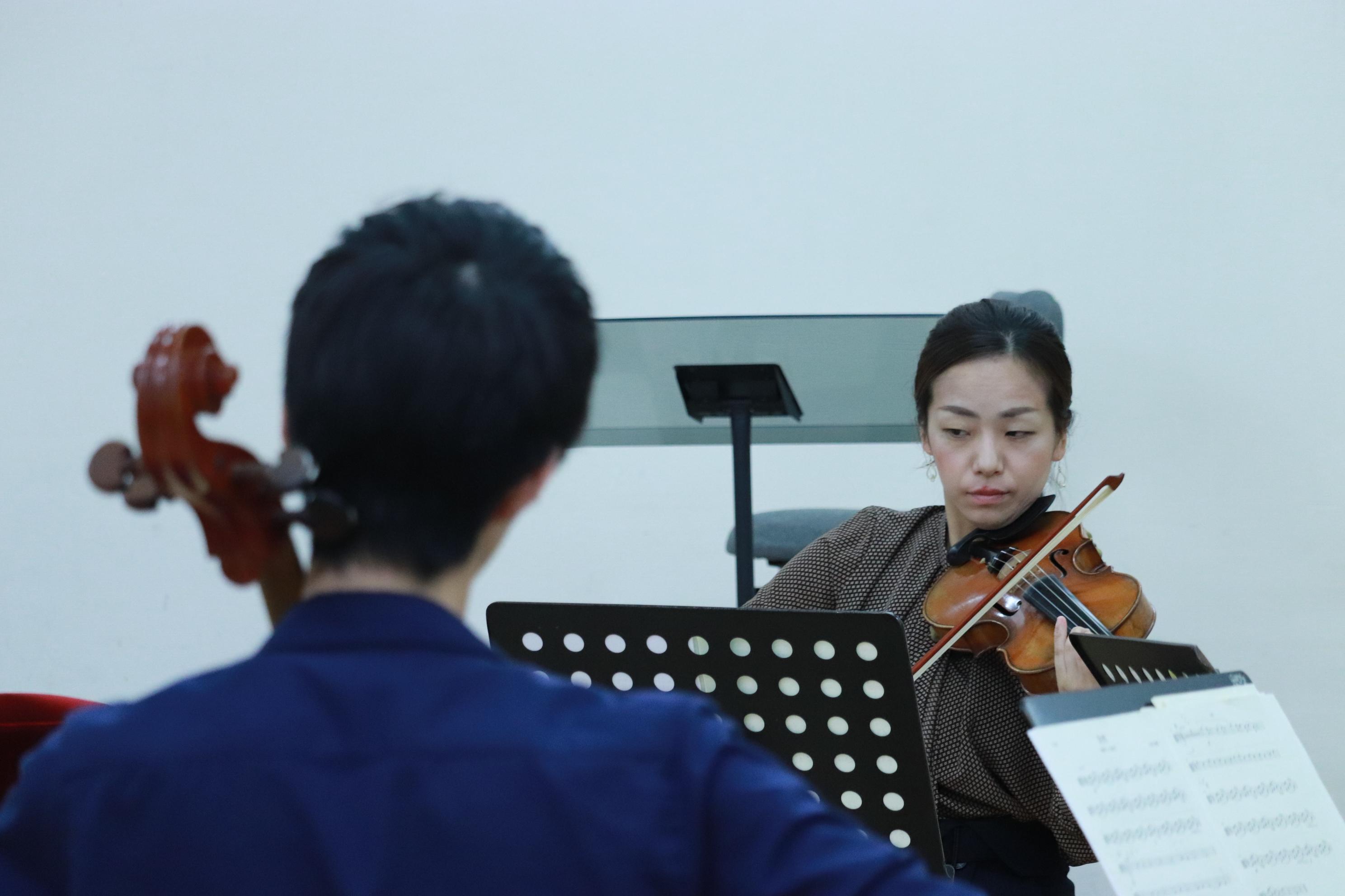 奥には先ほどのヴァイオリン奏者の女性。向かい合う形で、手前にチェロ奏者の男性の後姿。