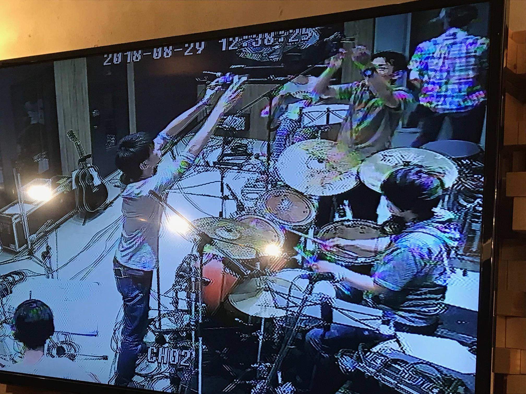 国立音楽院レコーディングスタジオの様子をコントロールルームに映し出すモニターの写真。学院生達がドラムにマイクを立てています。