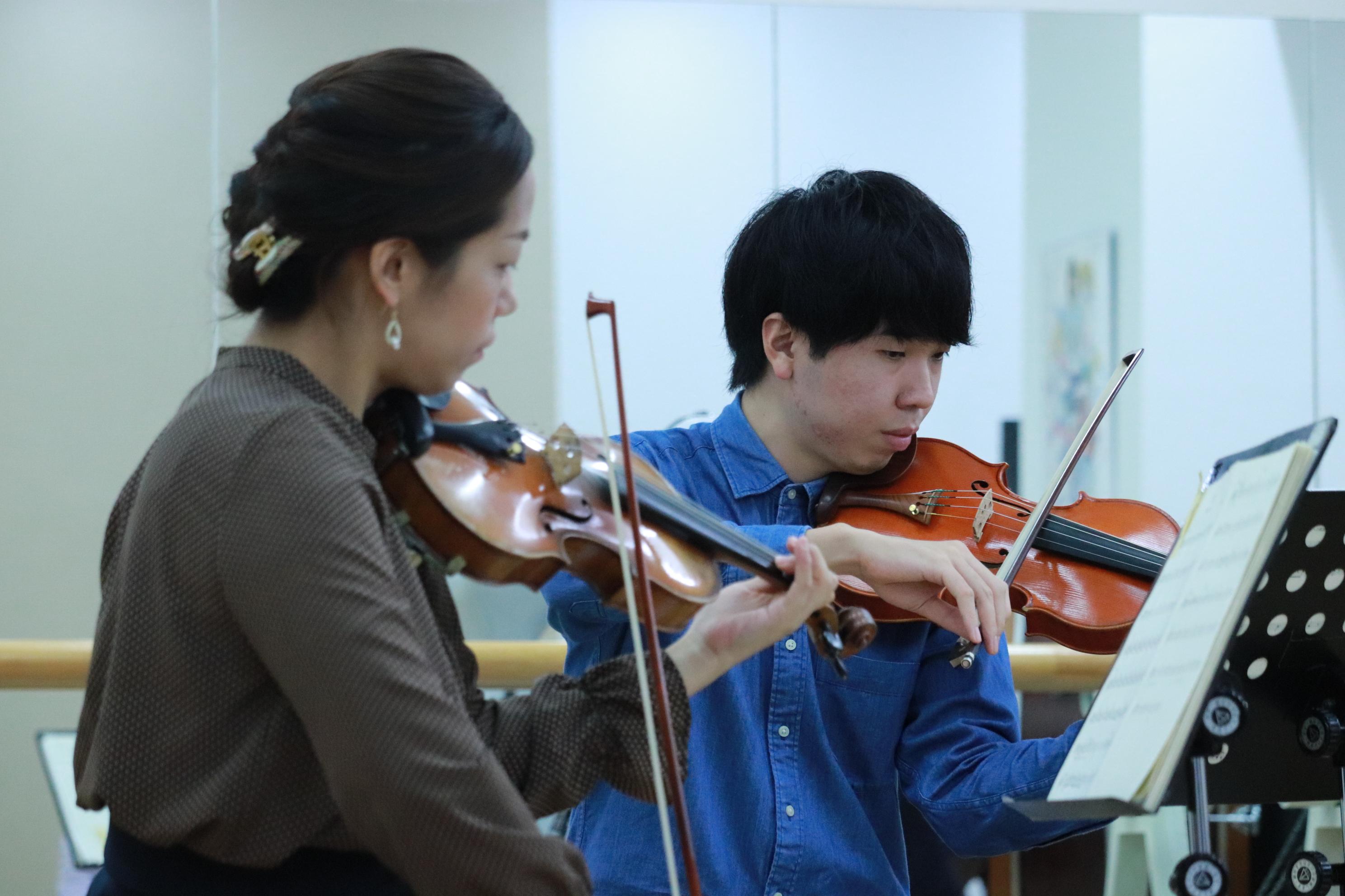 ヴァイオリン奏者の女性・男性を撮影した横からのアングル。