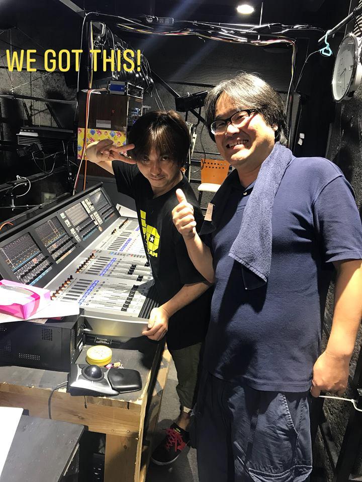 国立音楽院パラダイスホールのデジタルミキサーを前に笑顔でポーズをとるレコーディングエンジニア花島氏と国立音楽院で音響講師を務める河辺真先生。