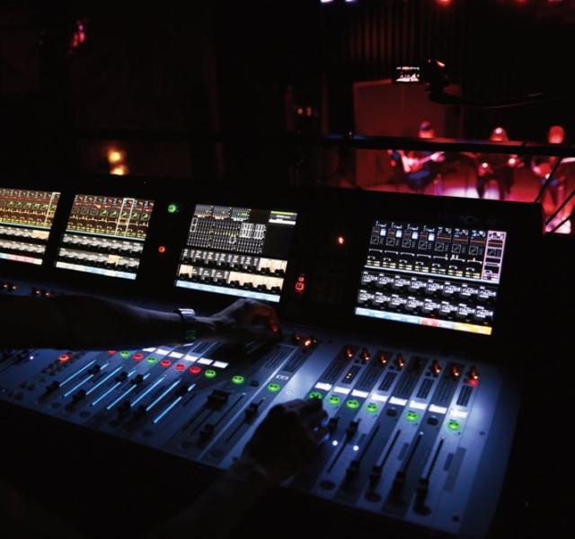 音響デザイン科のイメージ画像。国立音楽院 東京校地下一階にあるライブ施設「パラダイスホール」の音響機材を操作している様子。奥には照明に照らされたステージが見える。