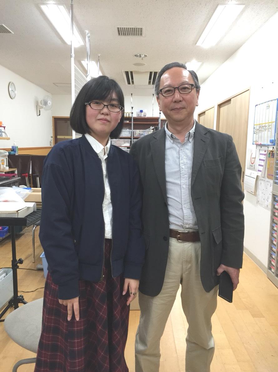 日谷晃講師と卒業生のツーショット写真。