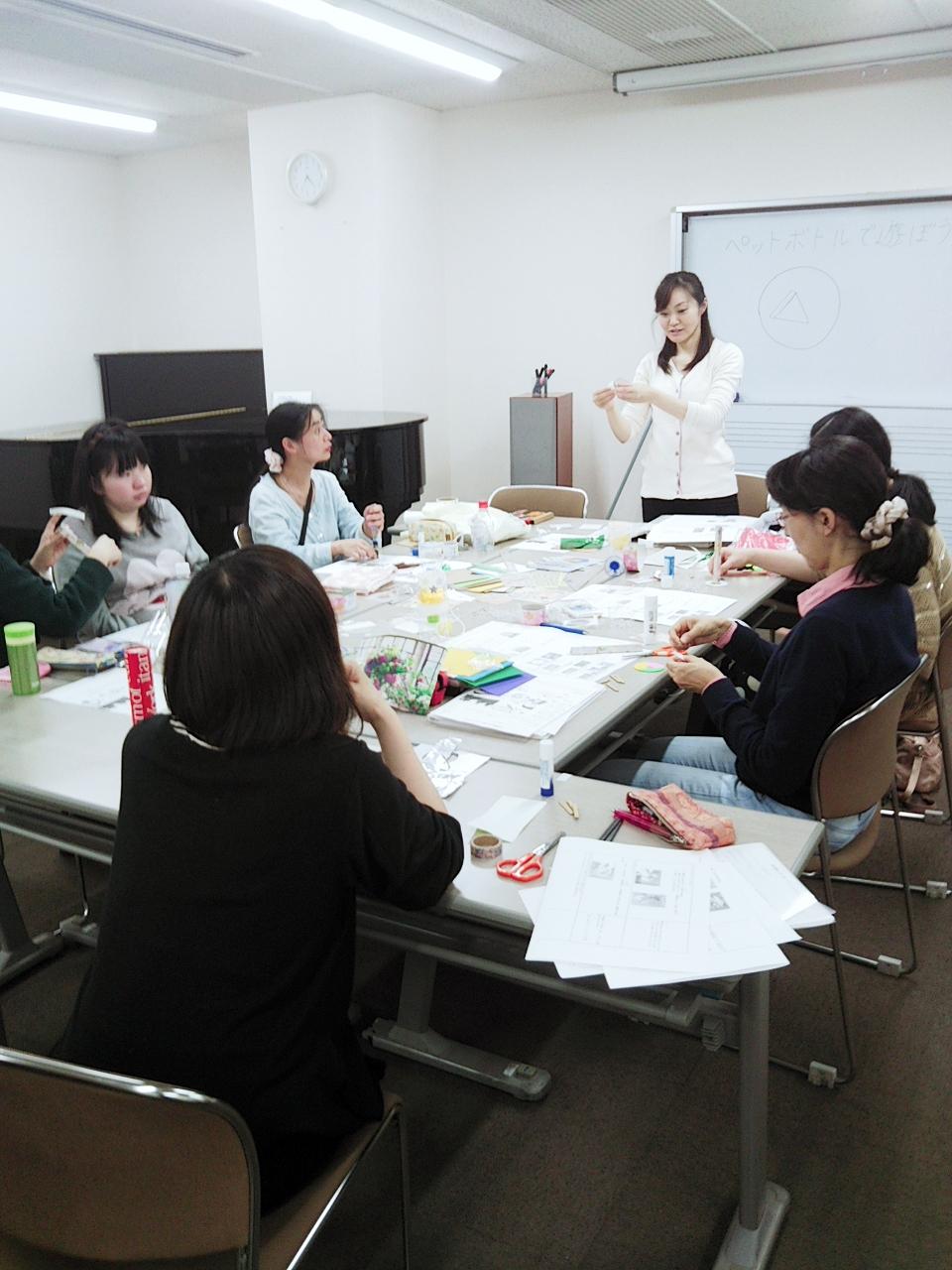 机を囲む田村講師と6名ほどの履修生の姿が映る。机の上には紙や文房具が沢山並んでいる。