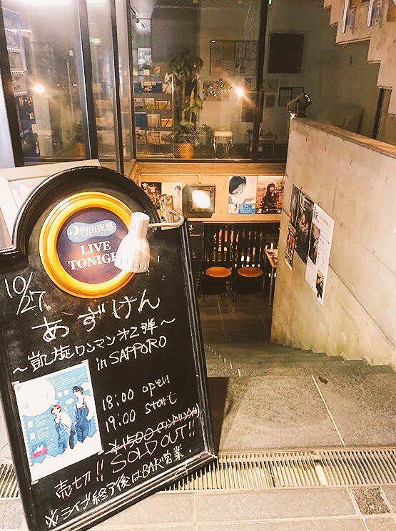 会場となったマルヤマノクターンの入口写真。看板には手書きで公演概要が書かれている。