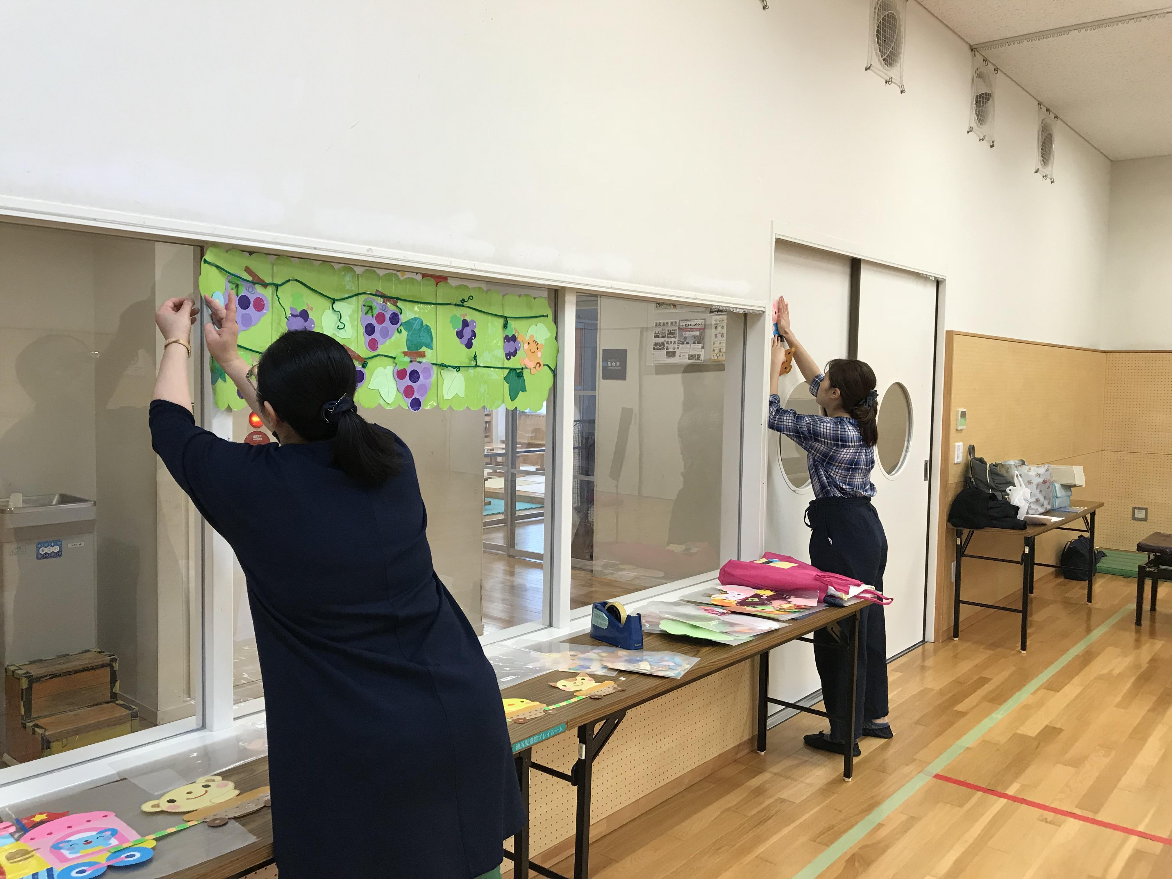 壁面装飾準備を進める様子。ピアノ伴奏を担当する先生と現場実習生の姿が写っています。