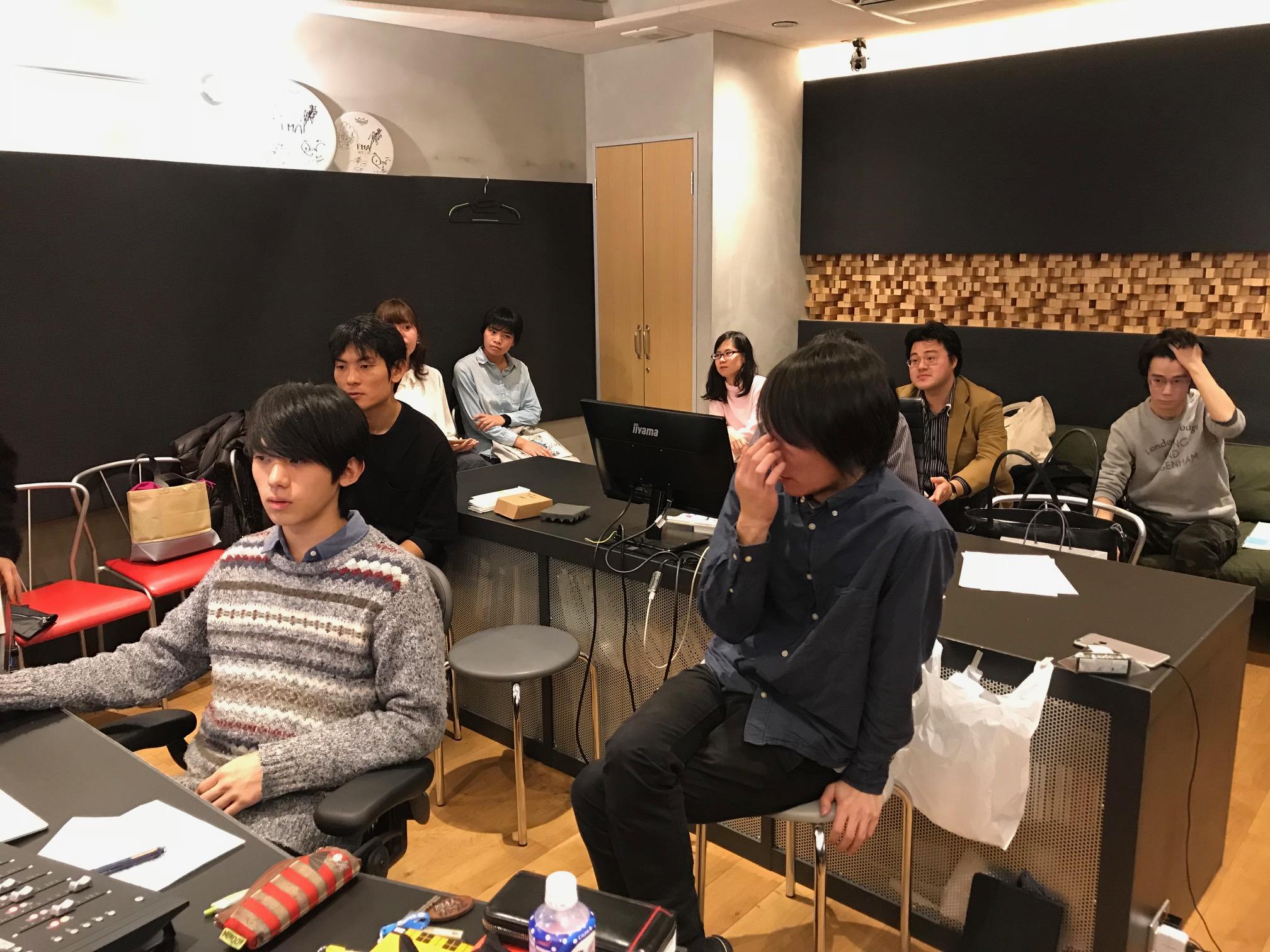 国立音楽院レコーディングスタジオのコントロールルームで演奏を聴く参加者数名。レコーディングエンジニアは吉崎拓郎先生が見守る中、学院生が担当しています。