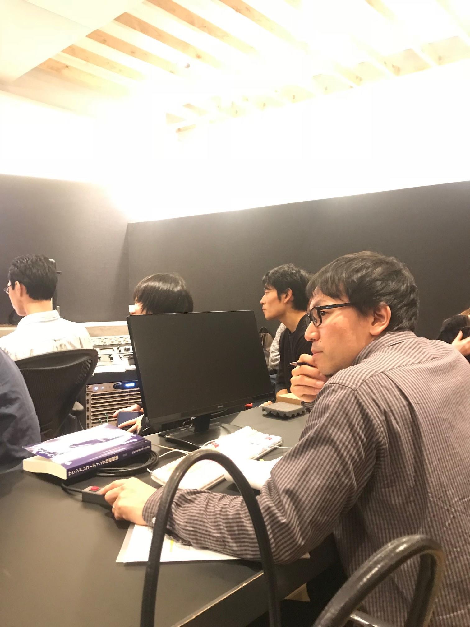 コントロールルームで作曲した学生達へ指示を飛ばす、国立音楽院の指導講師・大曽根浩範先生。画像奥には音響を学ぶ履修生の姿も見える。