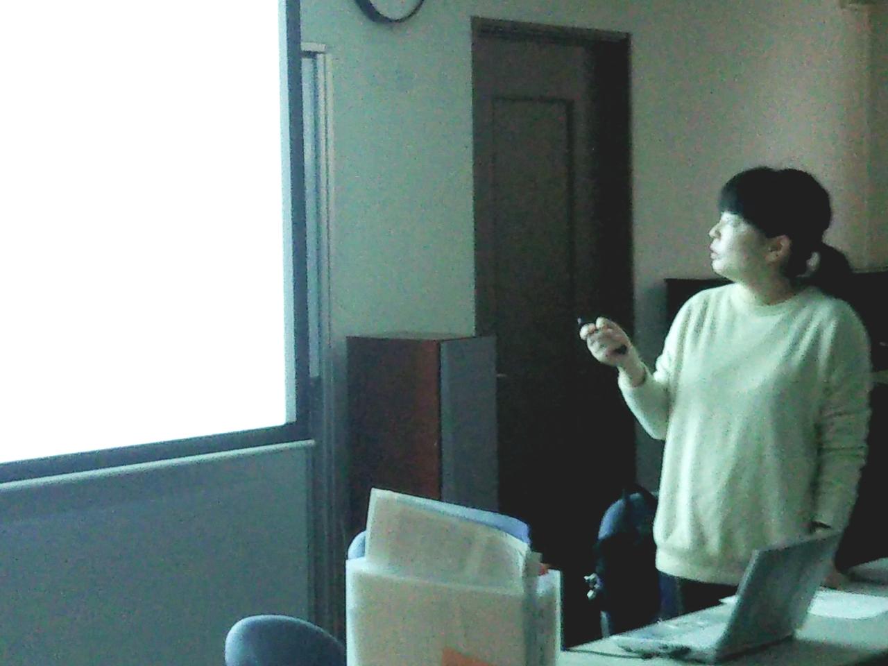 秋山友美講師が教室のプロジェクターでスクリーンに資料を映し出しながら講義を進めています。