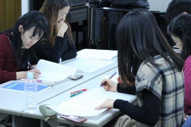 履修生と共にアイデアを練る種ともこ先生が映っています。皆さん真剣な表情で手元の譜面に書き込みを加えています。