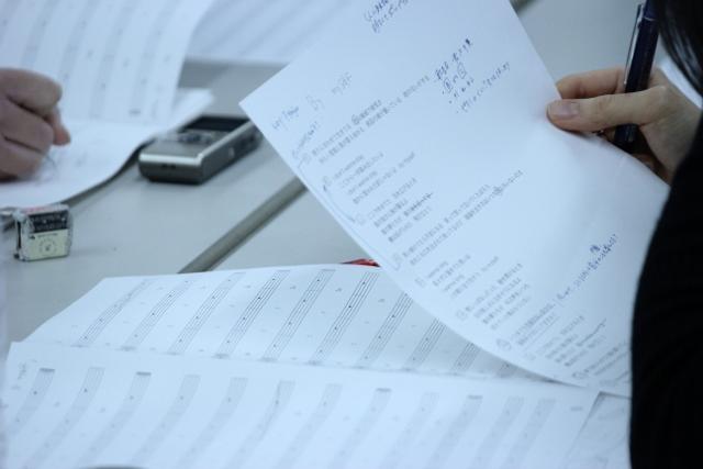 履修生の意見が反映された歌詞カードや五線譜に書き込みを加える学院生の手元を映した写真。