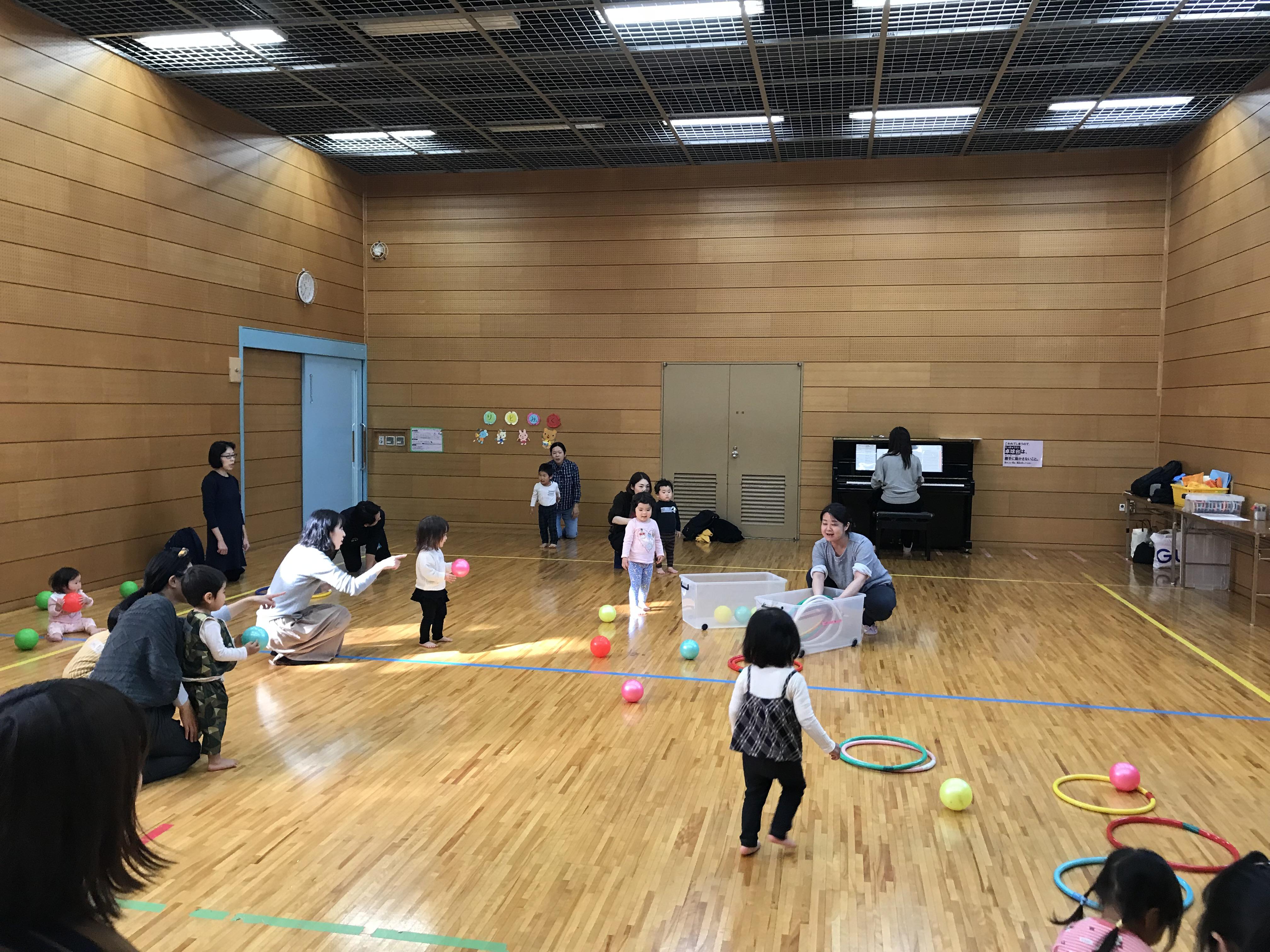 教室が始まるまではそこらじゅうに置かれていたボールやフープ。遊んでいた子ども達も、先生の見本を見ながらお片付けボックスへ持っていきます。