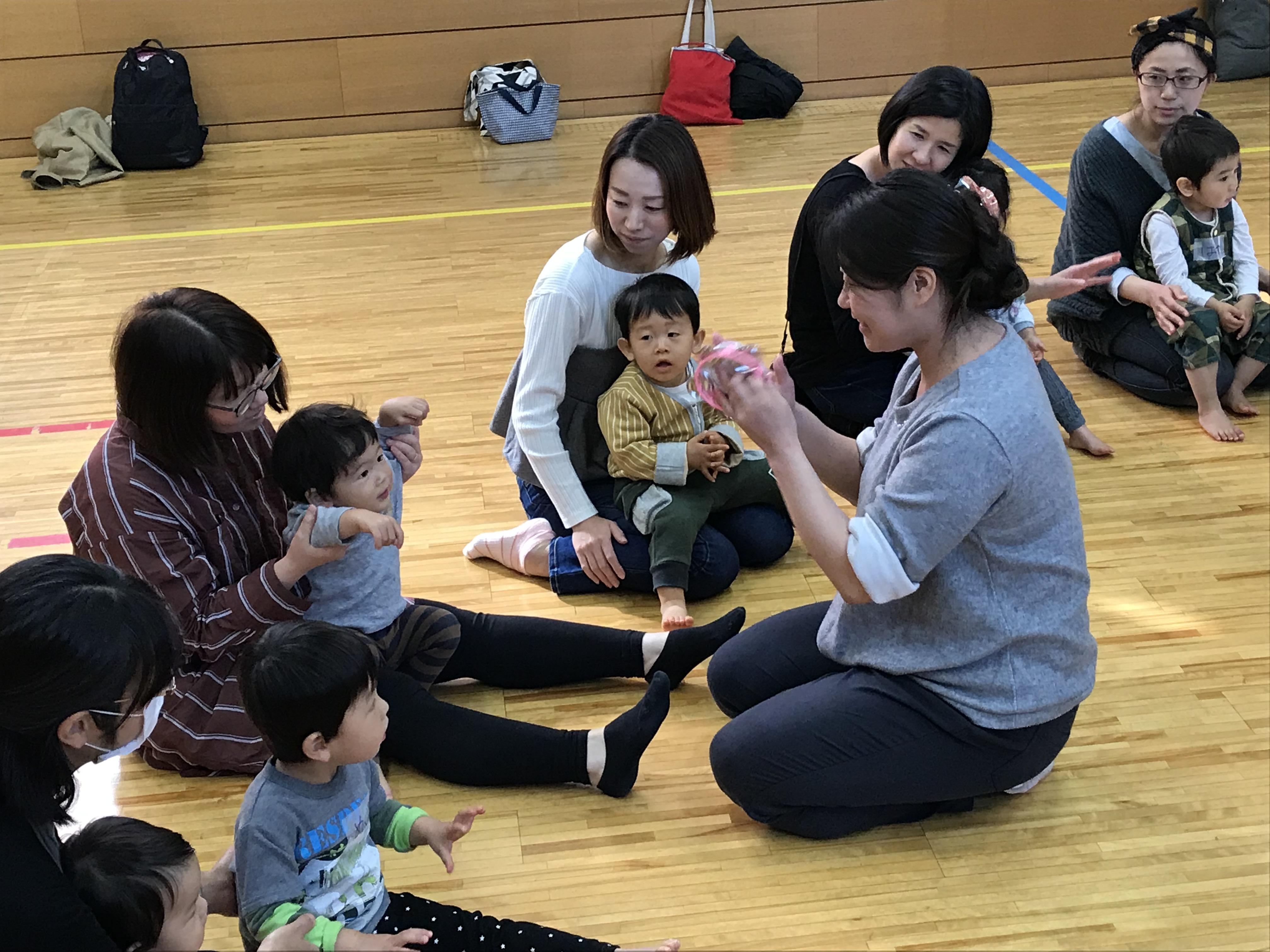 お行儀よくお母さんの膝に座る子ども達。輪になって一人一人、リズムに乗せて順々に名前を呼ばれていきます。お友達の様子を皆も優しく見守っています。