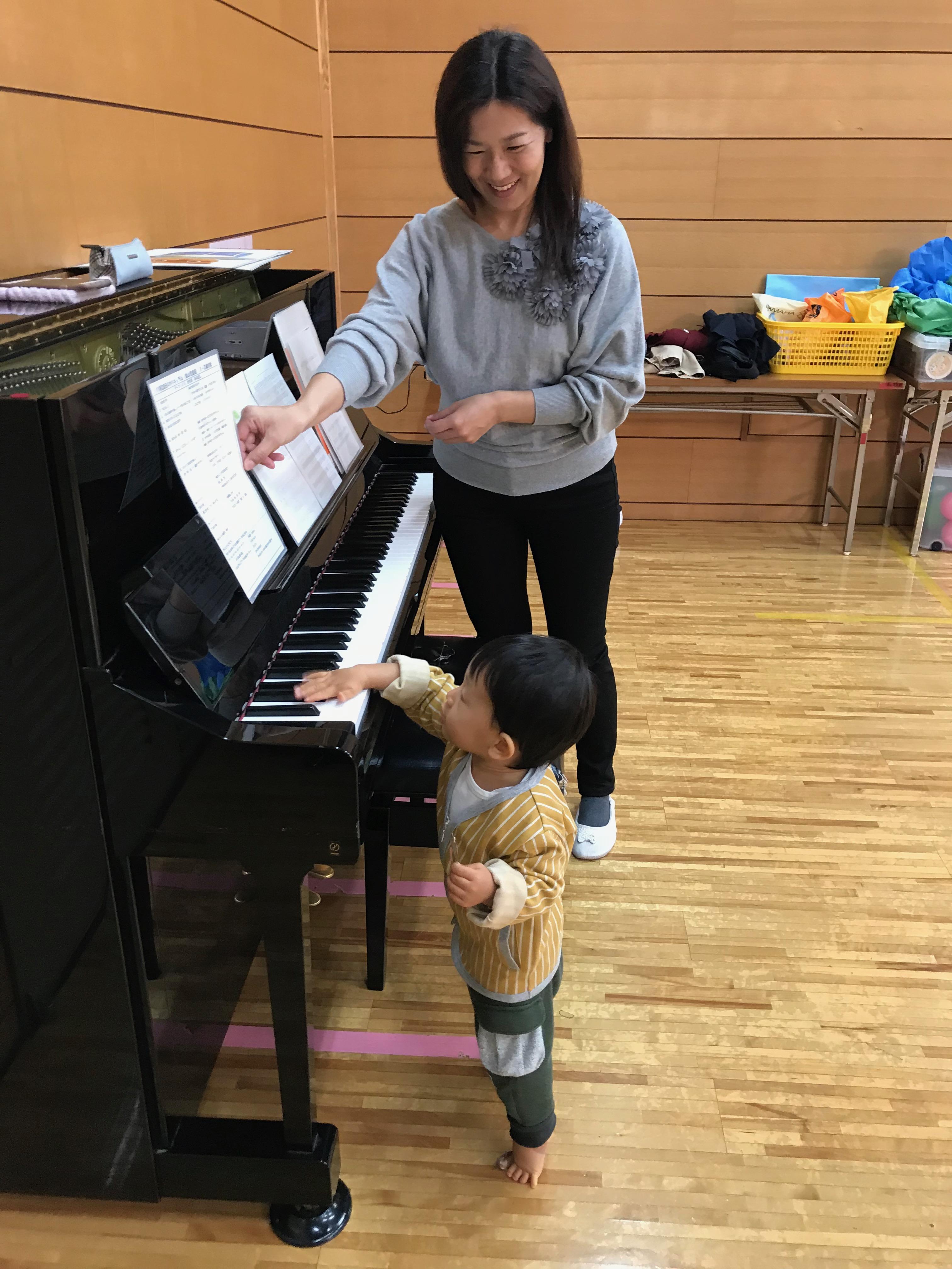 伴奏を務めた先生が、興味しんしんな様子でピアノ鍵盤に触れる男の子を笑顔で見守っています。