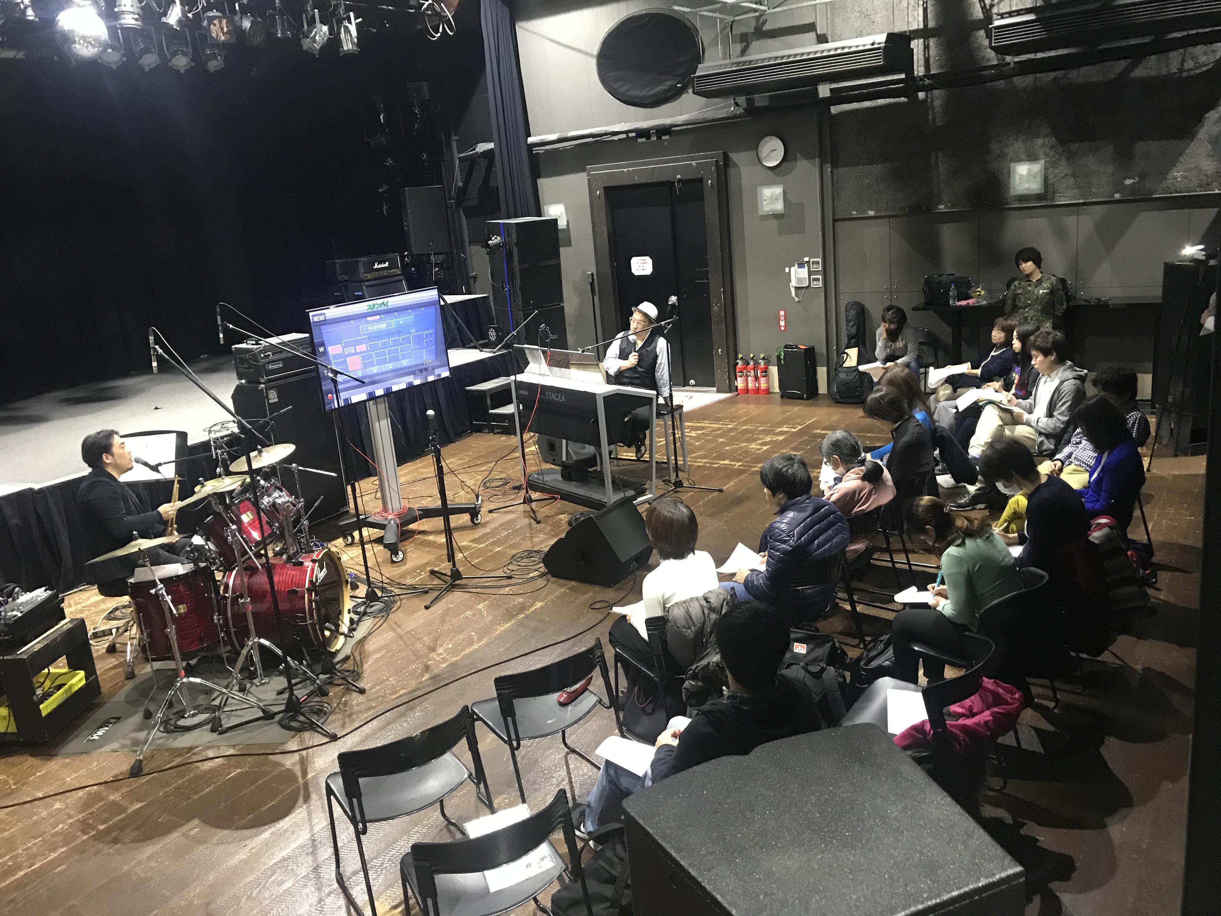 国立音楽院パラダイスホール。ステージではなく客席にドラムとエレクトーンを置き実演を交えながら講義を進めるオータケハヤト講師とおぎたひろゆき講師。参加者15名は配布された資料にメモを書き込んでいます。