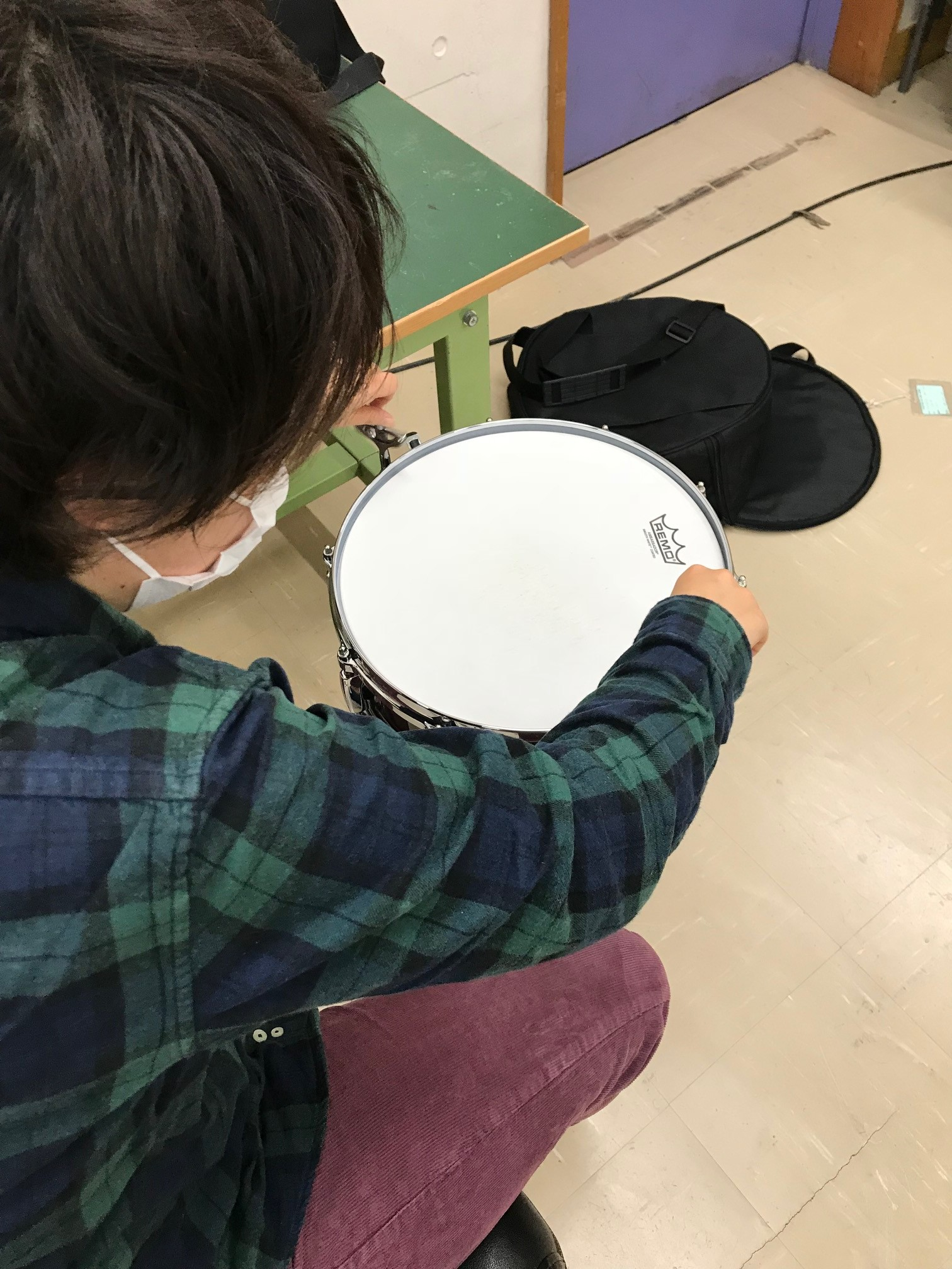 在校生がスネアをスタンドに設置している様子を、頭上から撮影した写真。