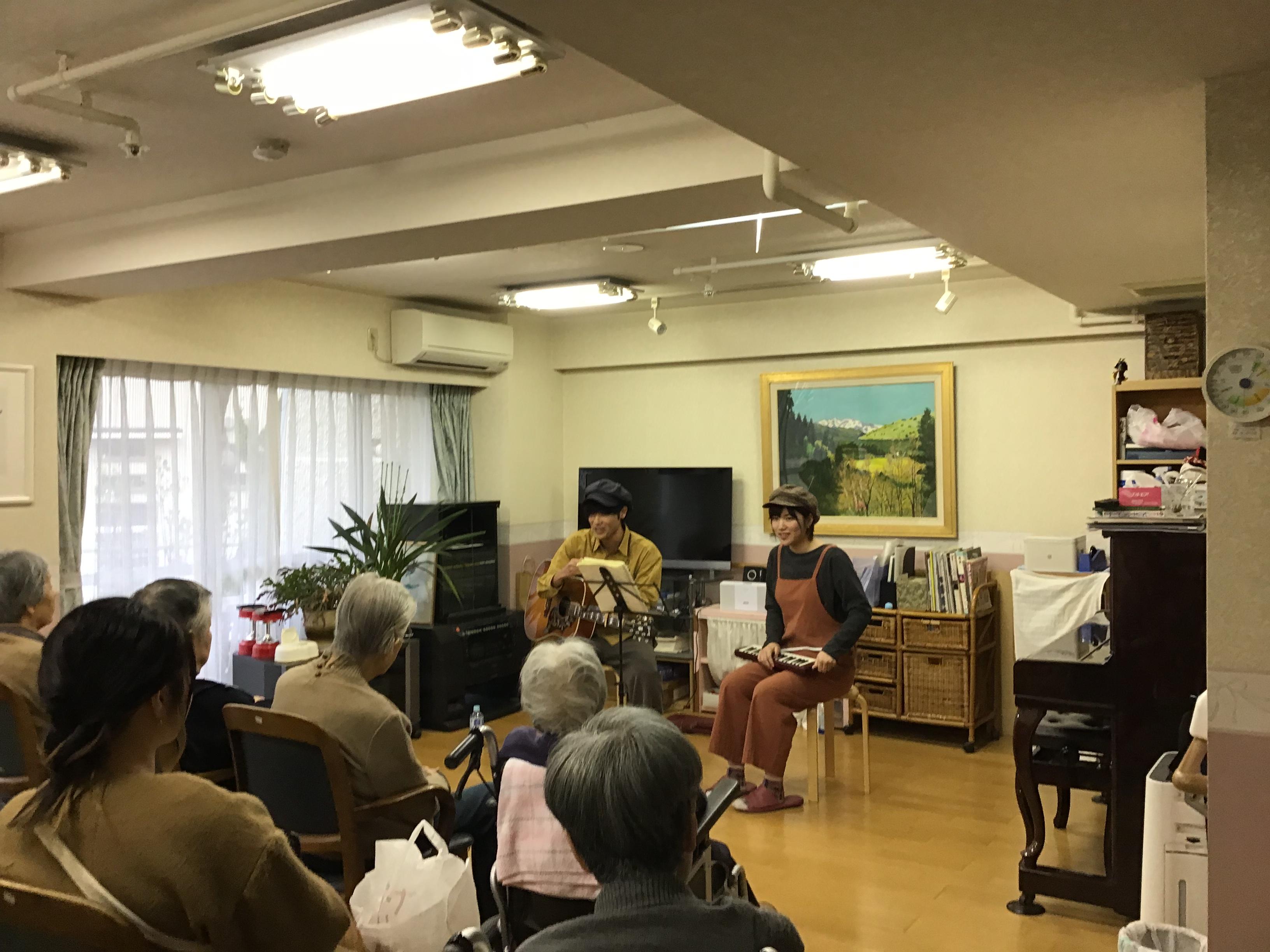 施設の高齢者の前で演奏をする「あずけん」の2人。武内君の手にはアコースティックギター、森田さんの手にはピアニカ。マイクを使わずに弾き語りライブを行いました。
