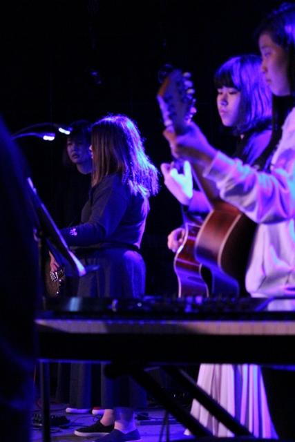 ステージ横から撮影された演奏中の風景。アコースティックギターやエレキギターを真剣な表情で演奏しています。