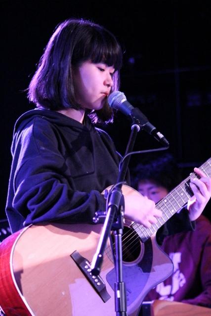 アコースティックギターを弾きながら歌っている女の子。奥にはキーボードを弾く男の子の姿も見えます。