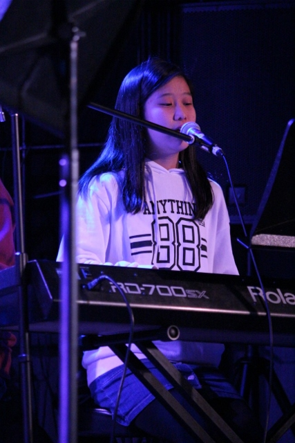 キーボードを弾きながらコーラスを歌う女の子。