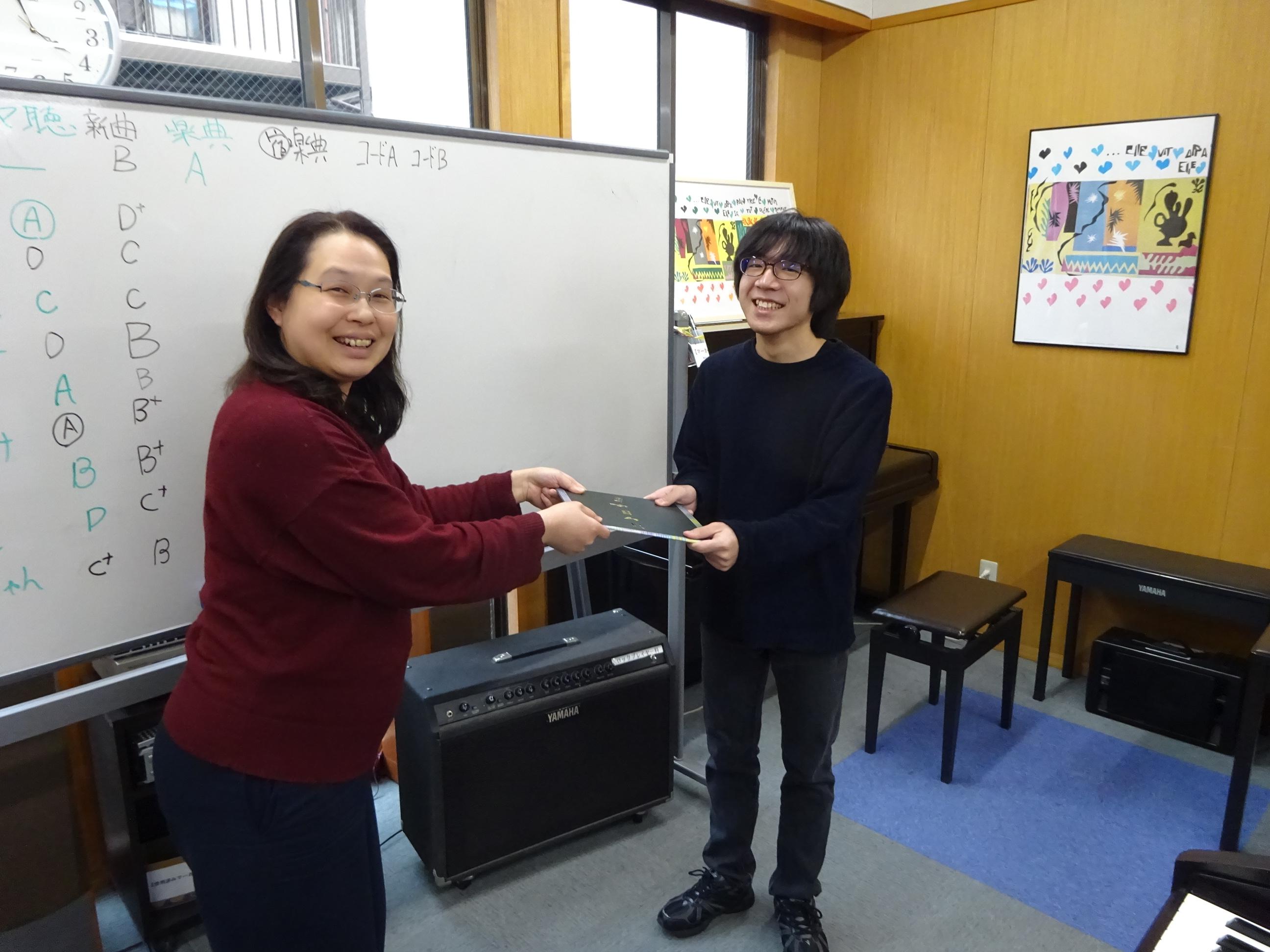 応援メッセージが書かれた寄せ書きを園田優講師から手渡される受講生。二人とも笑顔でカメラに目線を送っています。