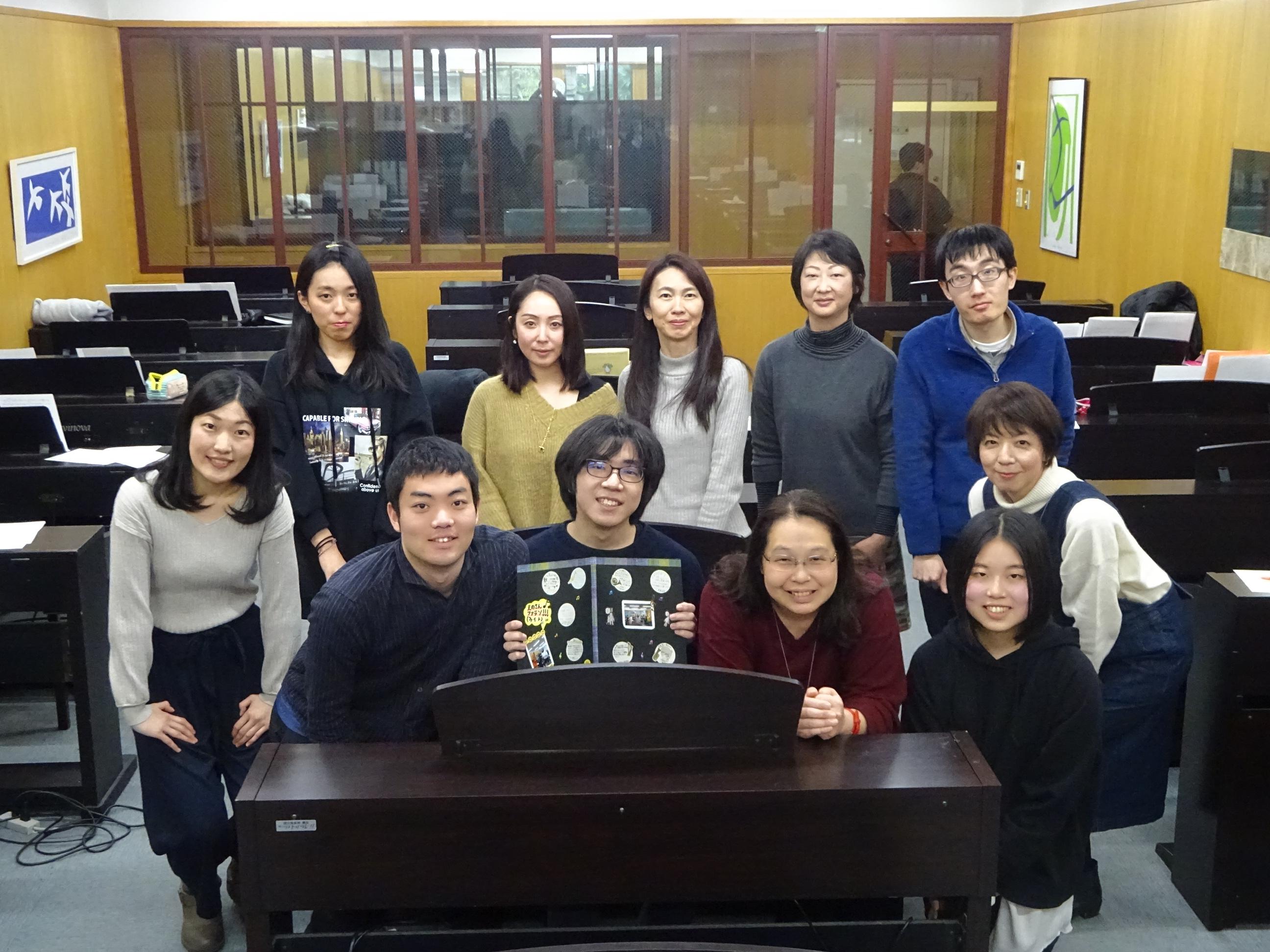 「音大受験実践講座」の受講生10名と園田先生の集合写真。数十台の電子ピアノが並ぶキーボードルーム内で撮影。