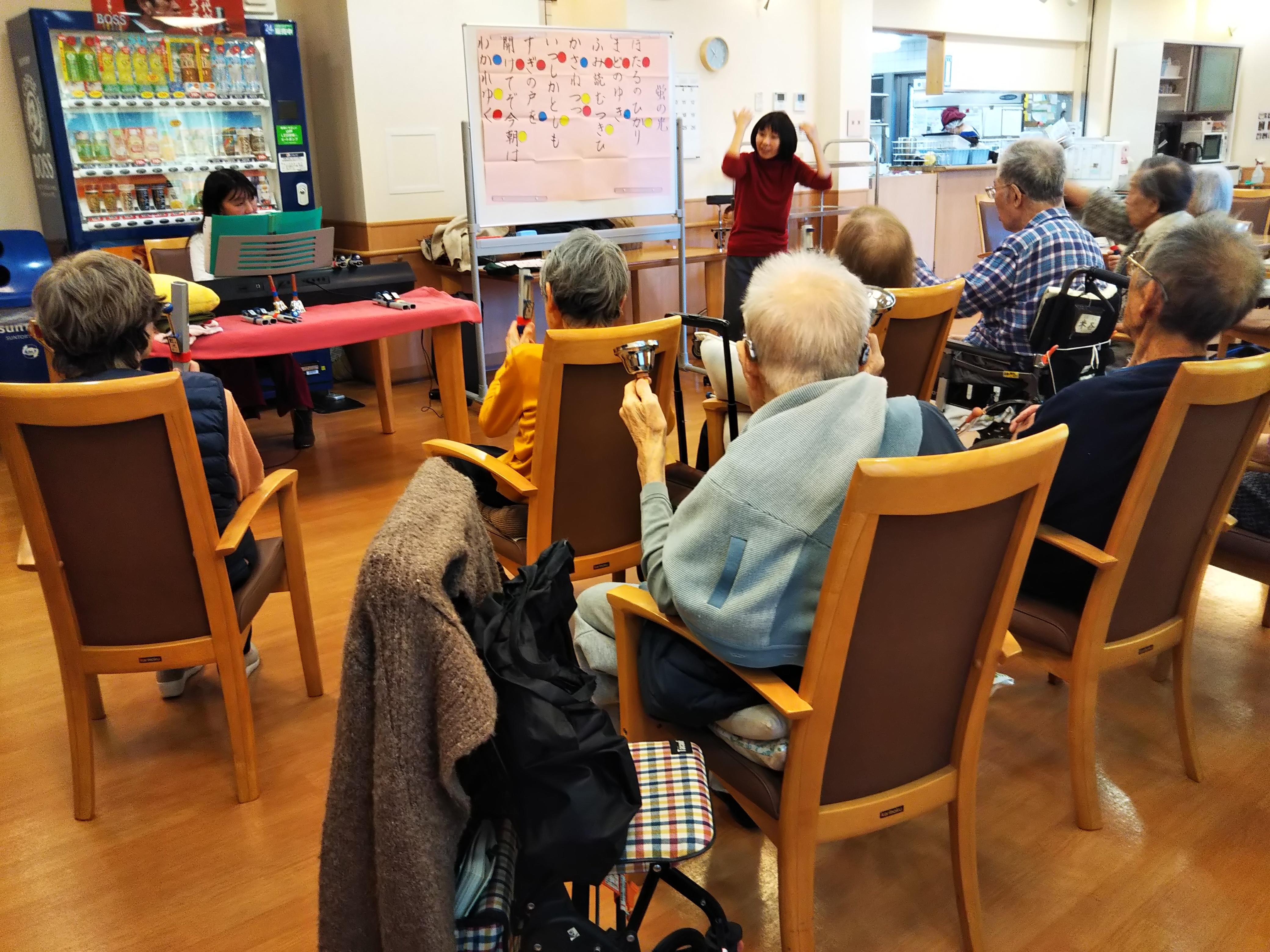 高齢者施設で行われている「若返りリトミック」の様子。ハンドベルなどを持ちプログラムを楽しむ参加者の方々。