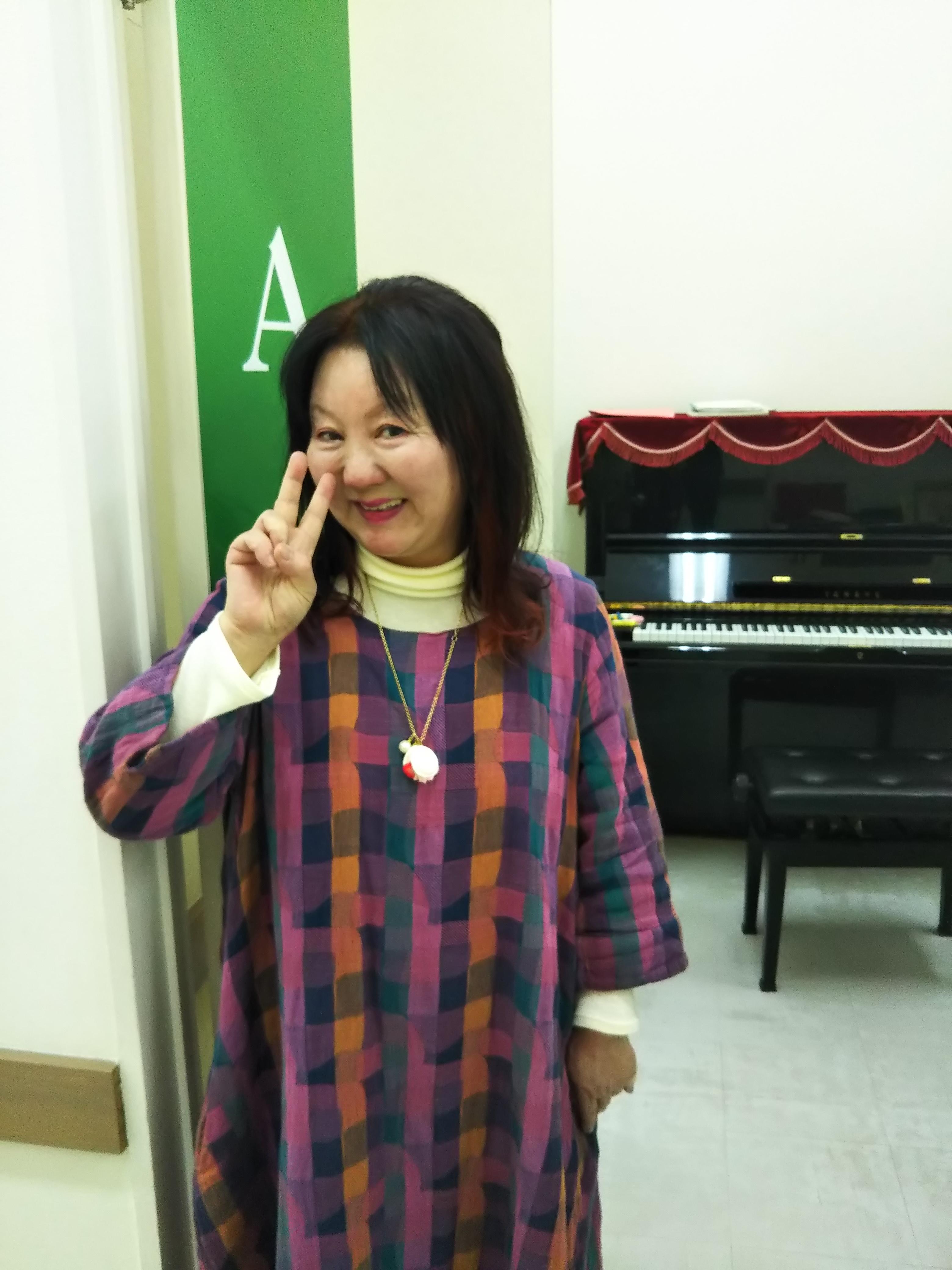 ピアノ演奏指導で活動している指導員さんの写真。ピースサインを作り笑顔で撮影。