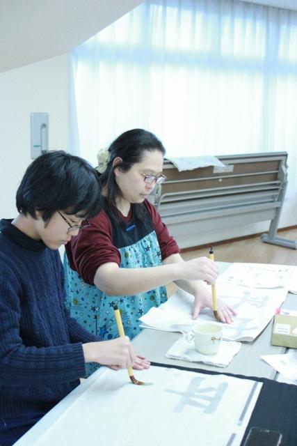 中等部2年生の男の子と園田優講師が筆を持ち、書初めをしている様子。