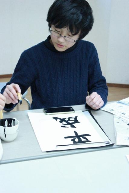中等部2年生の男の子が「平成」の文字を書き終えたばかりの写真。何度も練習したかいがあり、とても上手に書けています。