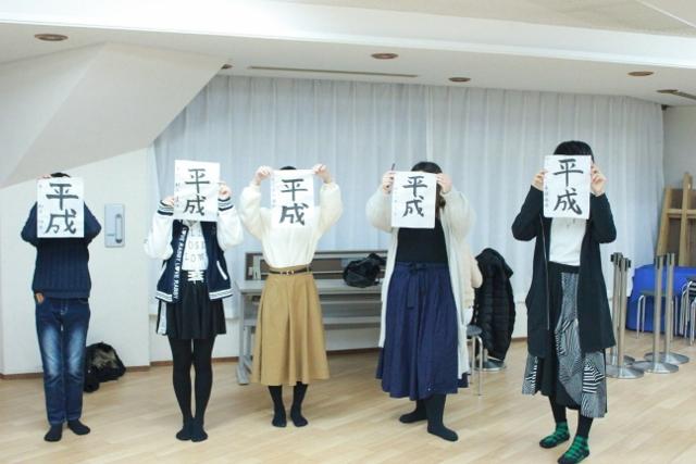 この日参加した中等部5名がカメラの前でポーズ。上手に書けた「平成」の文字を顔の前に掲げています。