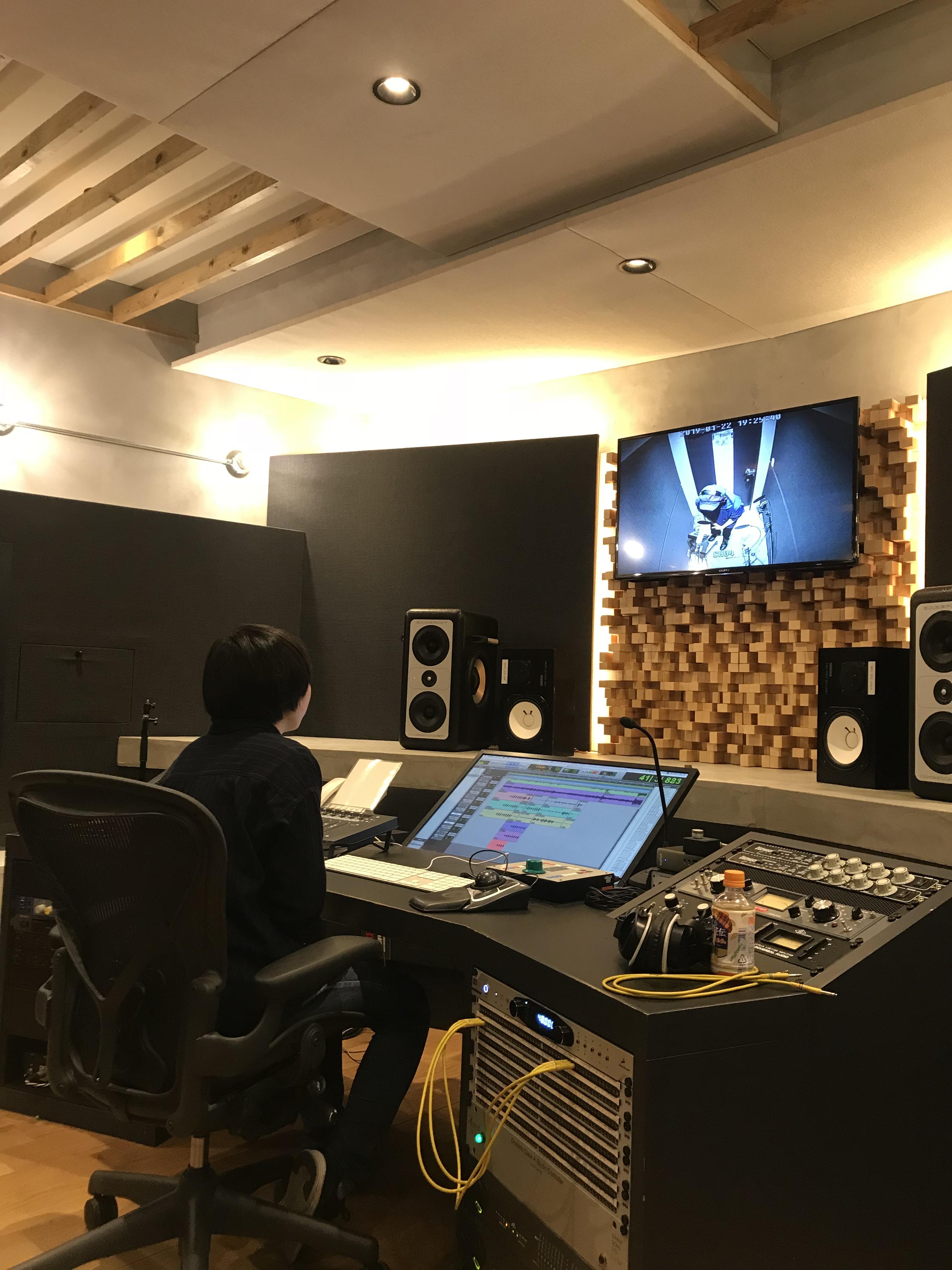 国立音楽院レコーディングスタジオのコントロールルーム。エンジニア席には音響デザイン科の2年生が座り、映像モニターには「あずけん」の武内建くんがヴォーカルブースで歌う姿が映し出されている。