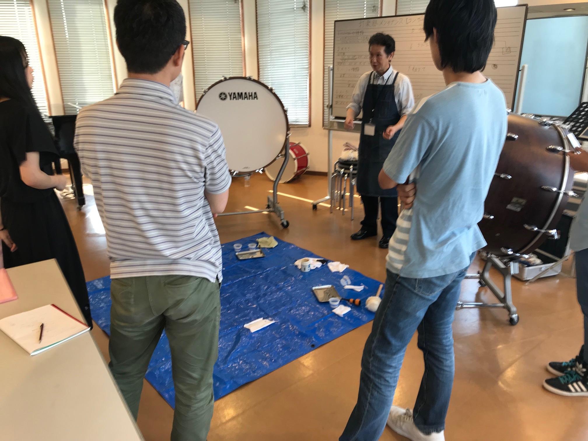 教室中央にブルーシートを敷き、パーツクリーニングをレクチャーする石井さんと参加者。